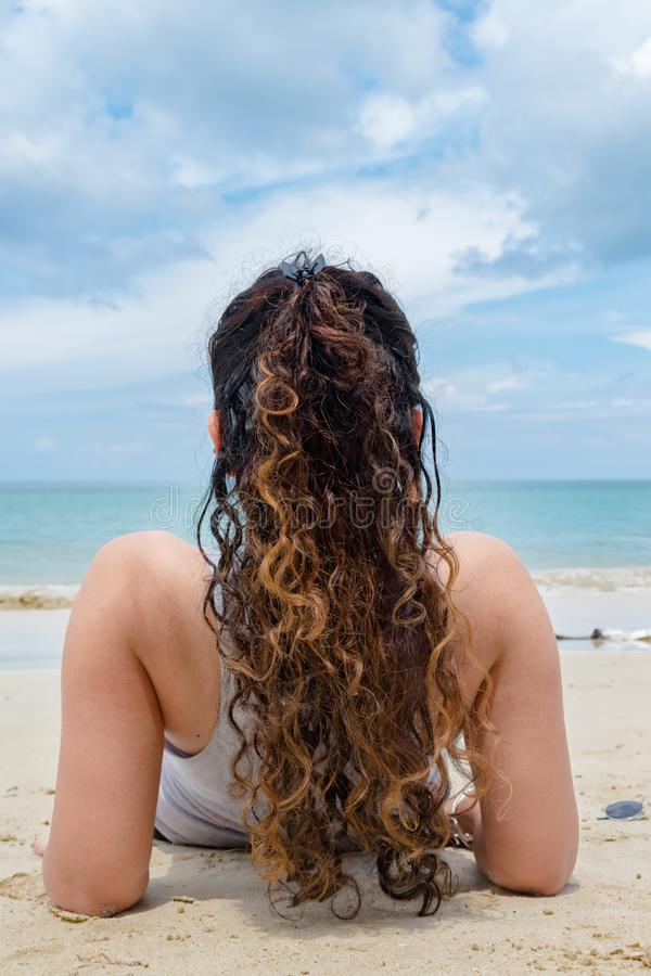 Tillbaka sikt av den ganska flådde flickan och att ha lockiga hår av guld- färg, solo koppla av & solbada på stranden på den exot arkivbild