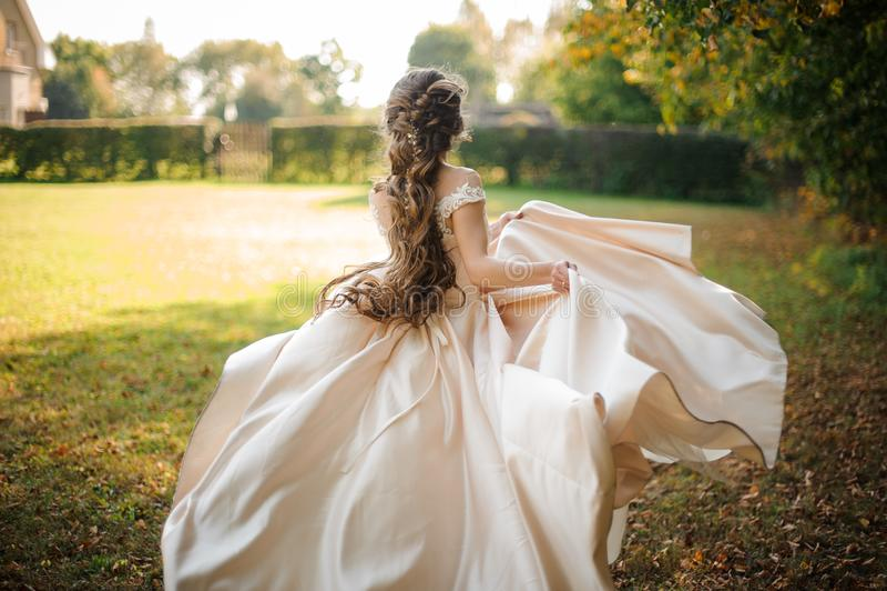 Tillbaka sikt av den härliga bruden som rotera i en bröllopsklänningdans på det gröna fältet royaltyfri bild