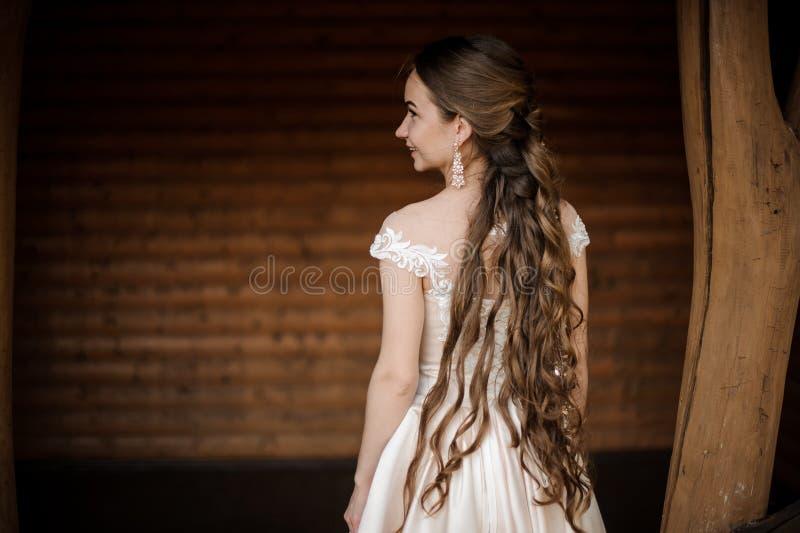 Tillbaka sikt av den härliga och le bruden i lång bröllopsklänning med en lång frisyr arkivbilder