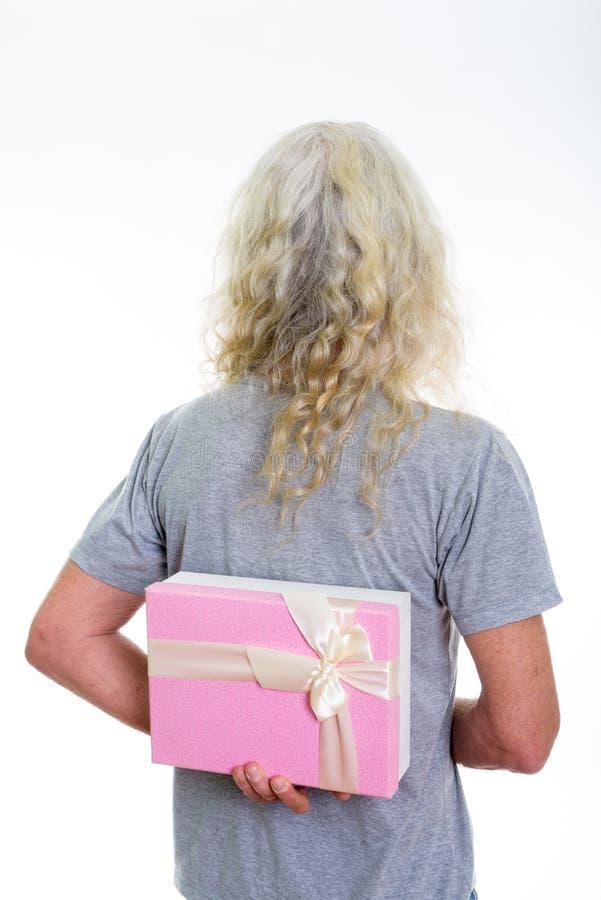 Tillbaka sikt av den höga skäggiga mannen som döljer gåvaasken bak tillbaka läsning arkivbild