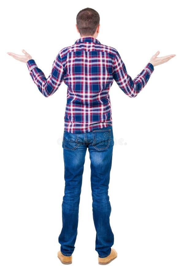 Tillbaka sikt av den ilskna unga mannen i jeans och rutig skjorta fotografering för bildbyråer