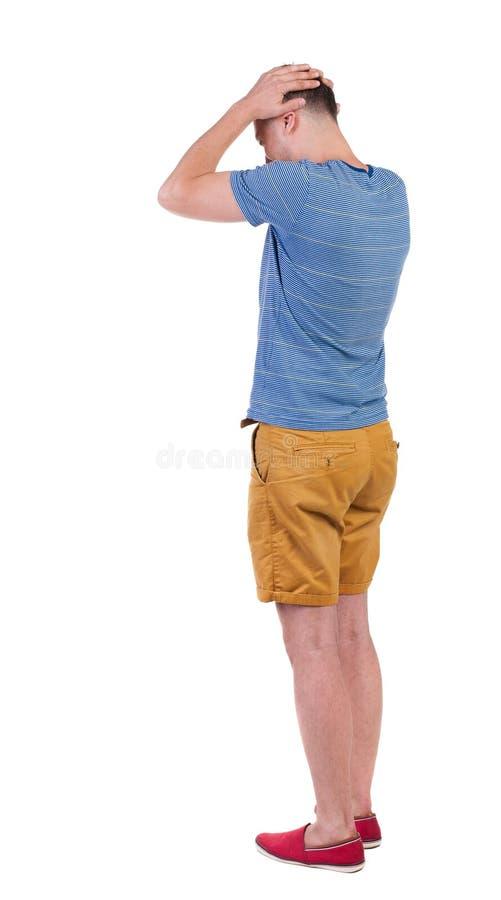 Tillbaka sikt av den ilskna unga mannen i kortslutningar och t-skjorta fotografering för bildbyråer