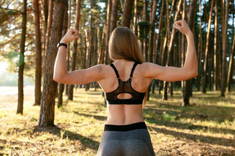 Tillbaka sikt av den kvinnliga visningen hennes muskler, utomhus arkivbilder