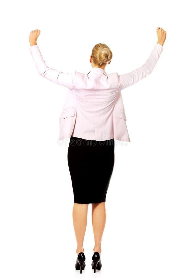Tillbaka sikt av den lyckliga affärskvinnan med armar upp royaltyfria foton