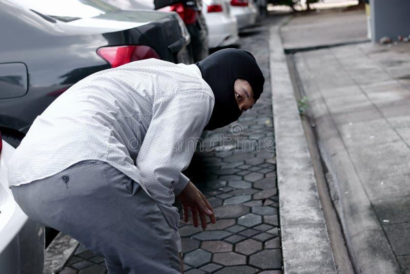 Tillbaka sikt av den maskerade tjuven i den svarta balaclavaen som försöker att bryta in i bilen Brottsligt brotts- begrepp fotografering för bildbyråer