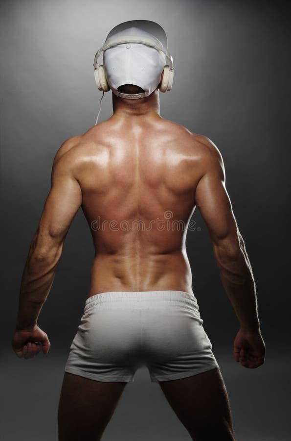 Tillbaka sikt av den muskulösa mannen med locket och hörlurar royaltyfria bilder