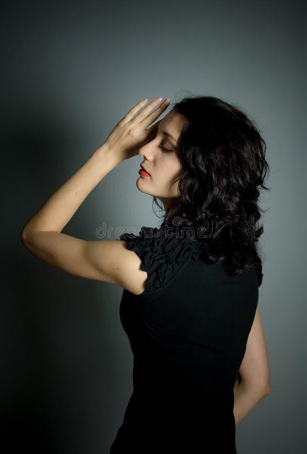 Tillbaka sikt av den nätta härliga unga flickan med röda sinnliga kanter och mörkt hår som poserar på svart bakgrund i studio arkivbild