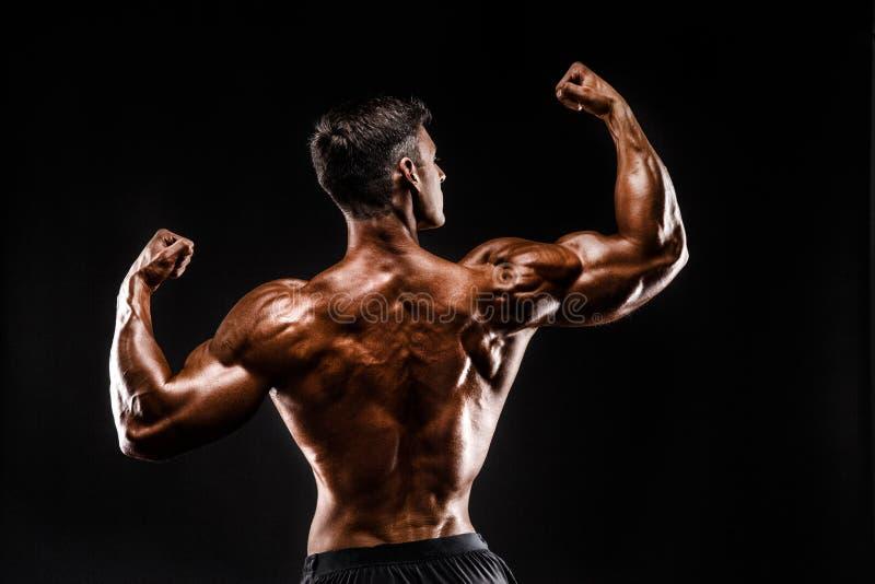 Tillbaka sikt av den oigenkännliga mannen, starka muskler som poserar med armar upp royaltyfria foton
