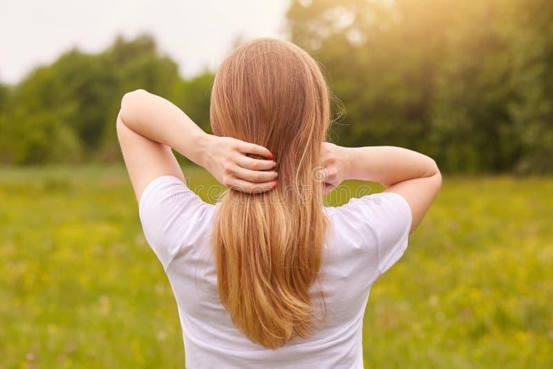 Tillbaka sikt av den oigenk?nnliga spensliga flickan som tycker om h?rligt landskap som st?r i mitt av den gr?na ?ngen, hennes l? royaltyfria bilder