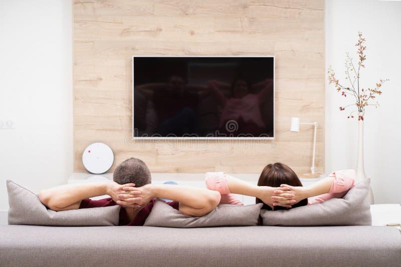 Tillbaka sikt av den parmannen och kvinnan som vilar i lägenhet och att sitta på soffan tillsammans och hållande ögonen på TV royaltyfria bilder