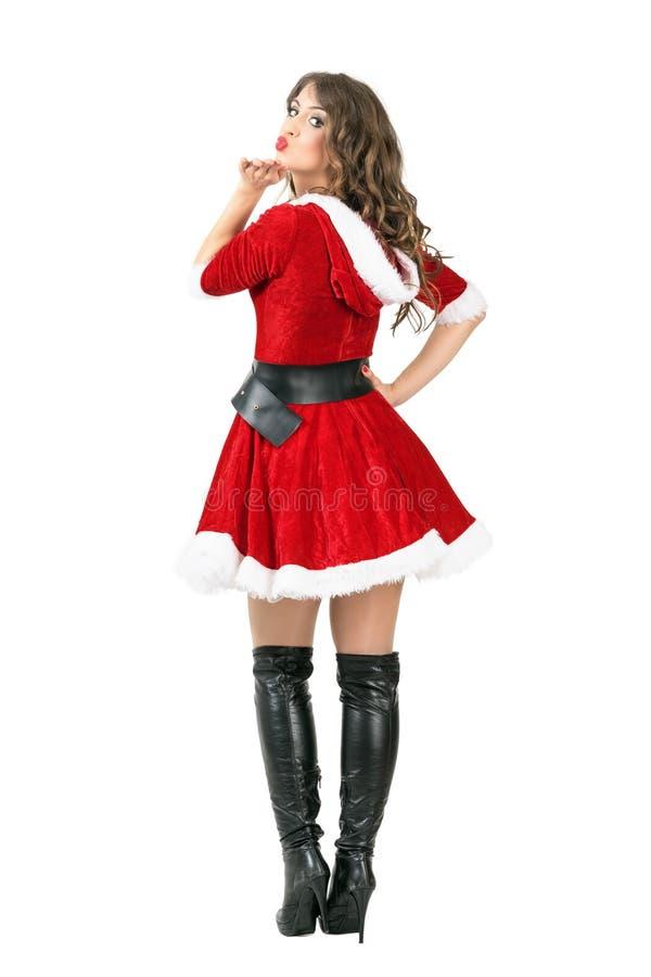 Tillbaka sikt av den sexiga attraktiva unga kvinnlign Santa Claus som blåser en kyss på kameran royaltyfri foto