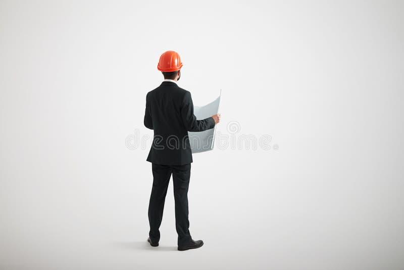 Tillbaka sikt av den stående mannen i formella kläder och en hård hatt fotografering för bildbyråer