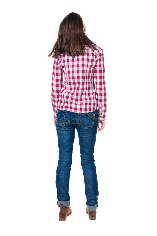 Tillbaka sikt av den stående unga härliga brunettkvinnan i kontrollör arkivbild
