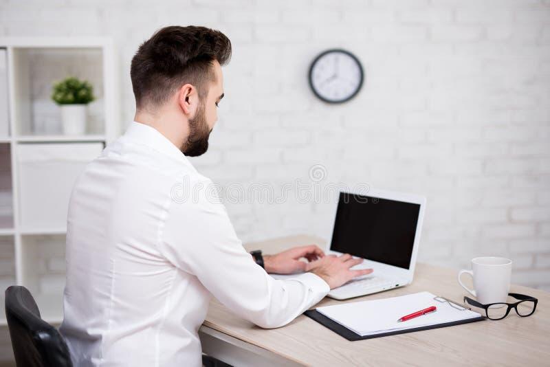 Tillbaka sikt av den stiliga affärsmannen som i regeringsställning använder bärbara datorn arkivbilder