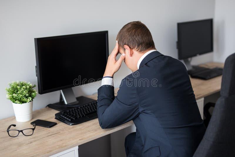 Tillbaka sikt av den stressade skärmen för PC för affärsman i regeringsställning - tomma med kopieringsutrymme royaltyfri fotografi