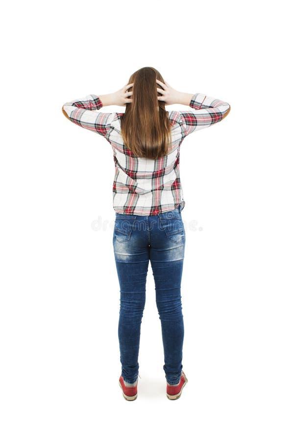 Tillbaka sikt av den tonårs- flickan som förväxlar Chockad tonårs- flicka med händer på huvudet Full längd arkivbild