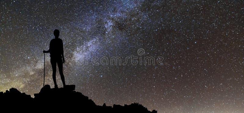 Tillbaka sikt av den turist- flickan för ung slank fotvandrare på överkant för stenigt berg på stjärnklar himmel för mörk natt oc arkivbilder
