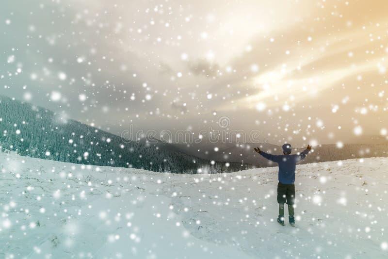 Tillbaka sikt av den turist- fotvandraren i varma kläder med ryggsäckanseende med lyftta armar på röjning som täckas med snö på p arkivfoton