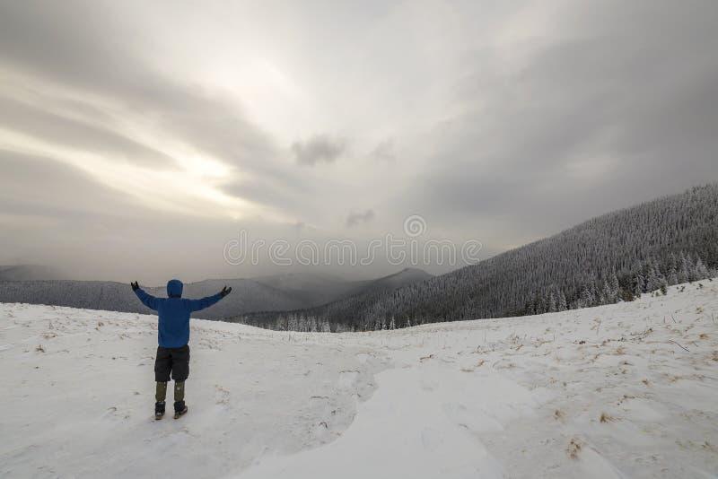 Tillbaka sikt av den turist- fotvandraren i varma kläder med ryggsäckanseende med lyftta armar på röjning som täckas med snö på p royaltyfri foto