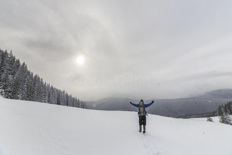 Tillbaka sikt av den turist- fotvandraren i varma kläder med ryggsäckanseende med lyftta armar på röjning som täckas med snö på p royaltyfria foton