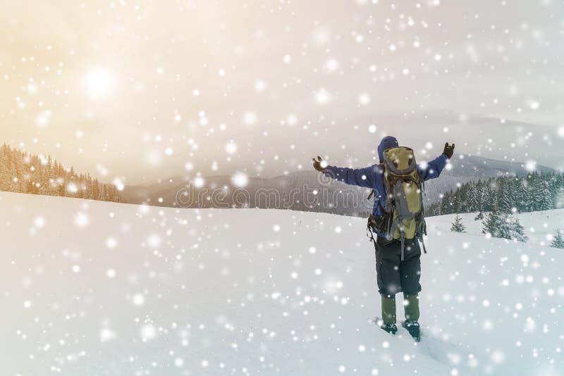 Tillbaka sikt av den turist- fotvandraren i varma kläder med ryggsäckanseende med lyftta armar på röjning som täckas med snö på p arkivfoto