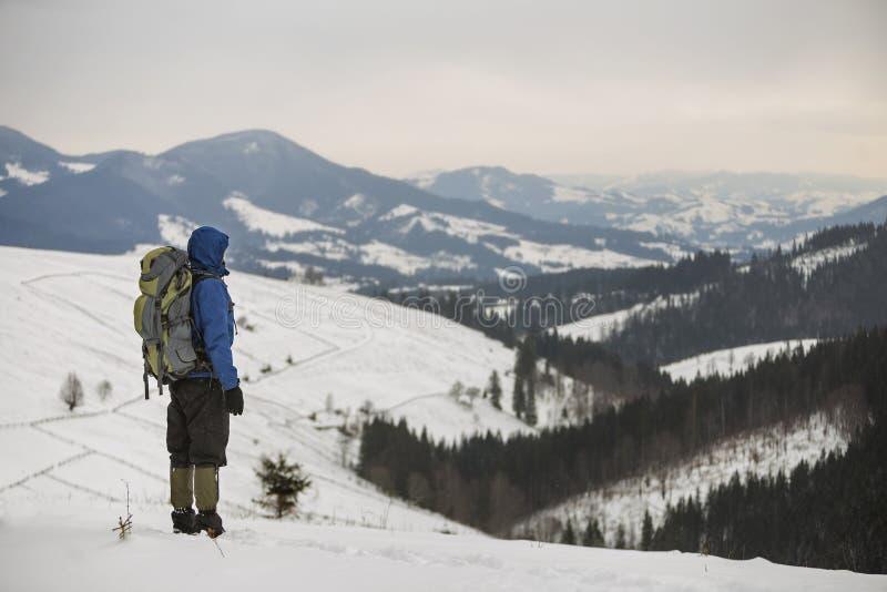 Tillbaka sikt av den turist- fotvandraren i varma kläder med ryggsäckanseende på bergröjning på kopieringsutrymmebakgrund av det  royaltyfri bild