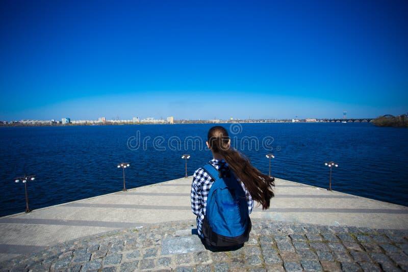 Tillbaka sikt av den turist- kvinnan med ryggsäcken som sitter på pir nära havet på solig dag royaltyfri fotografi