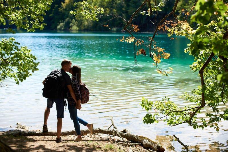 Tillbaka sikt av den turist- den parpojken och flickan med ryggsäckar som står på flodbanken royaltyfri fotografi