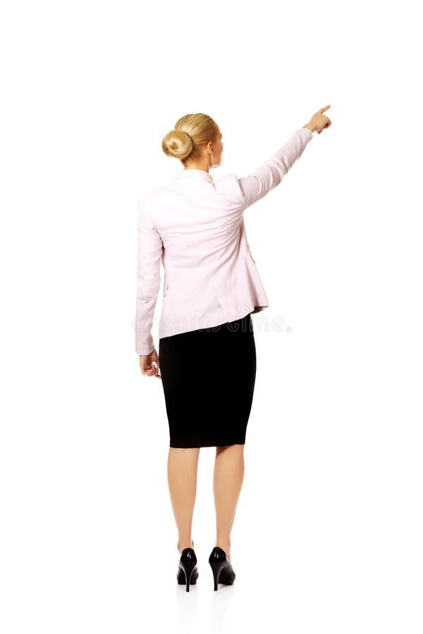 Tillbaka sikt av den unga affärskvinnan som pekar för somathing arkivbild
