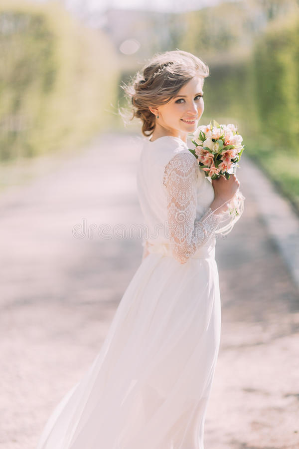 Tillbaka sikt av den unga blonda bruden i den vita klänningen med den brud- buketten som står utomhus- fotografering för bildbyråer