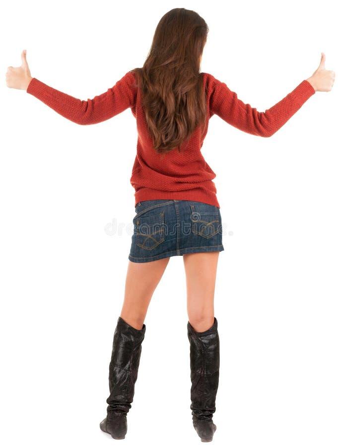 Tillbaka sikt av den unga brunettkvinnan, i jeans och att gå för tröja arkivfoton