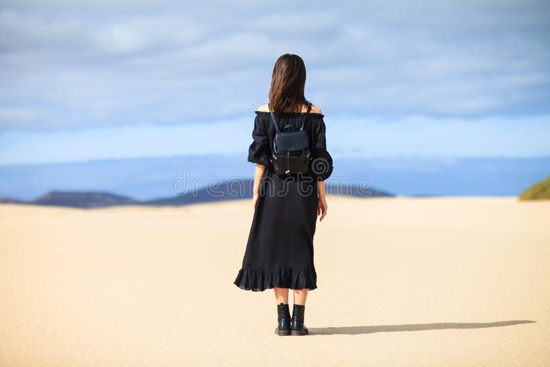 Tillbaka sikt av den unga ensamma kvinnan i lång svart klänning i öken på arkivbilder
