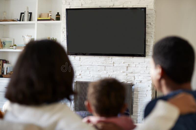 Tillbaka sikt av den unga familjen som tillsammans sitter på soffan och den hållande ögonen på TV:N i deras vardagsrum, slut upp, royaltyfri fotografi