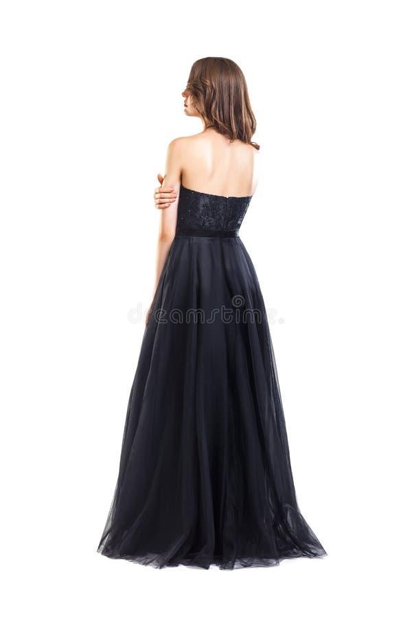Tillbaka sikt av den unga härliga kvinnan i svart aftonklänning arkivfoto