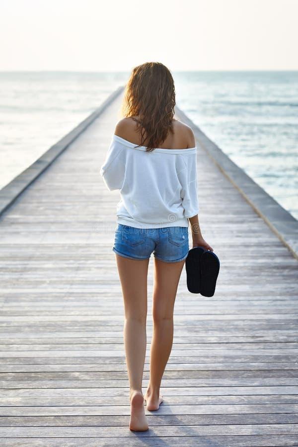 Tillbaka sikt av den unga härliga kvinnan som går på pir royaltyfri foto
