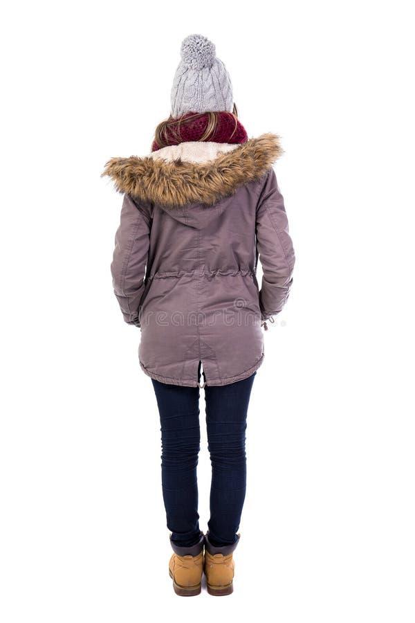 Tillbaka sikt av den unga kvinnan i vinterkläder som isoleras på vit royaltyfria foton