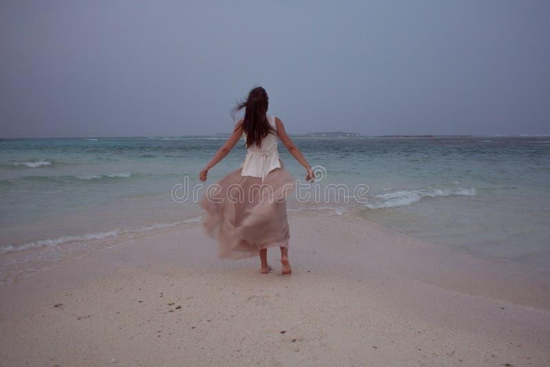 Tillbaka sikt av den unga kvinnan mot en havshorisont Brunettflicka i det vita kjolflyget på vind arkivbilder
