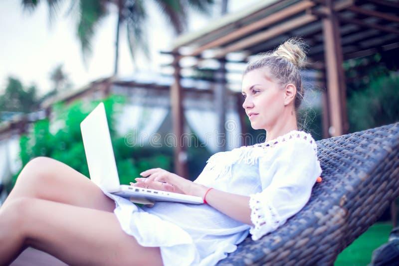 Tillbaka sikt av den unga kvinnan som gör avlägset arbete på modern bärbar datorwhil fotografering för bildbyråer