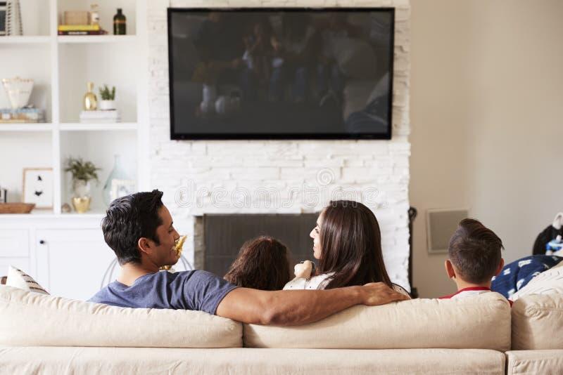 Tillbaka sikt av den unga latinamerikanska familjen av fyra som sitter på den hållande ögonen på TV:N för soffa, mum som ser fars royaltyfri fotografi