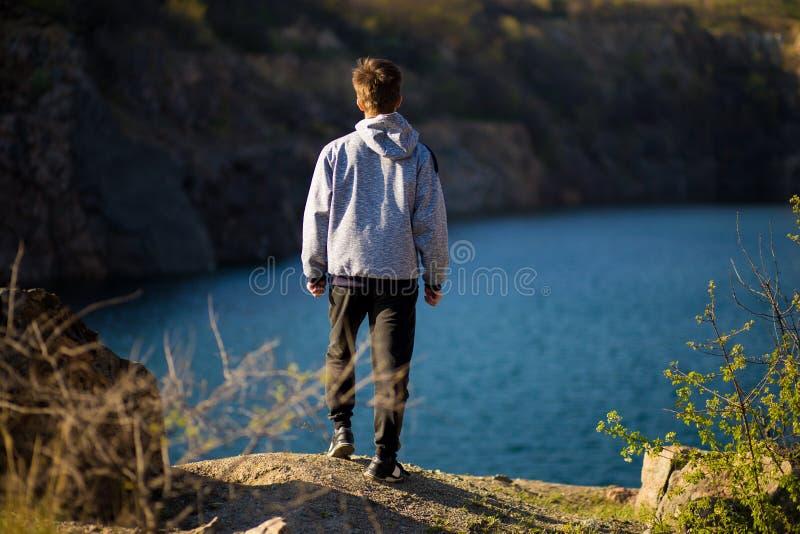 Tillbaka sikt av den unga mannen som ser den härliga sikten på sjön Lopp- och psykologibegrepp royaltyfria bilder