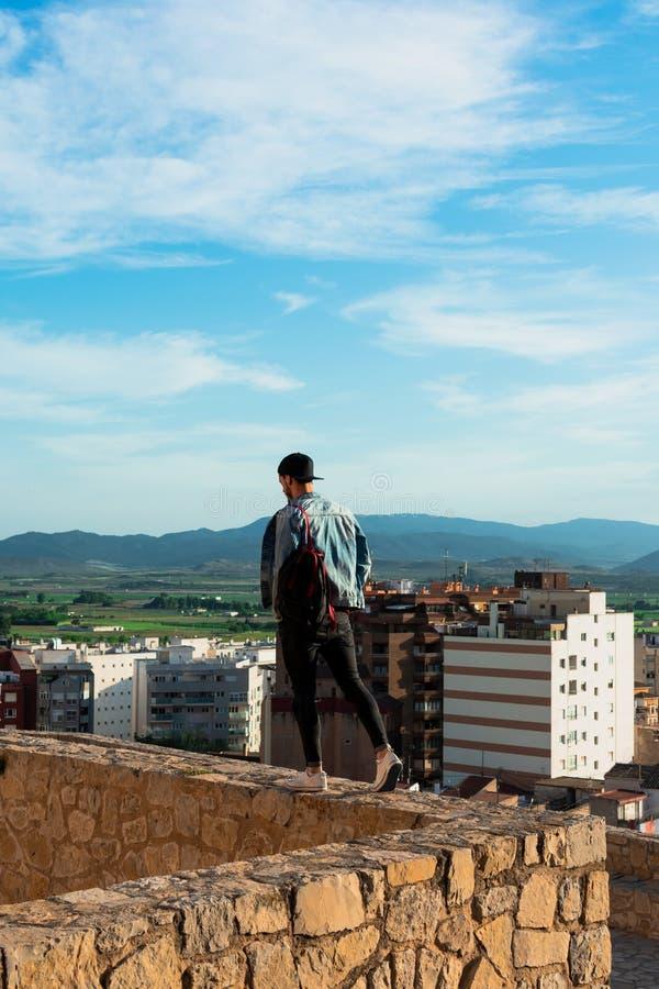 Tillbaka sikt av den unga mannen som ser staden fr?n slotttak royaltyfri bild