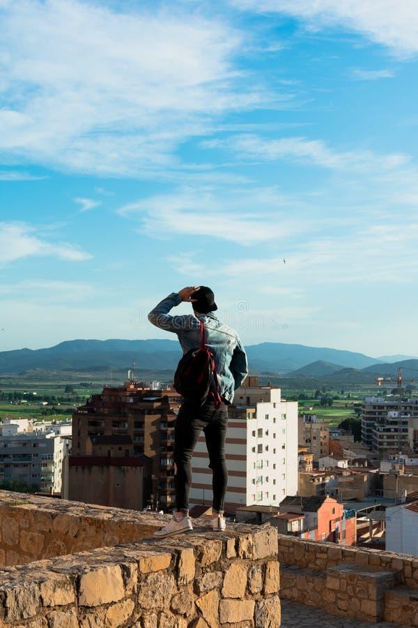 Tillbaka sikt av den unga mannen som ser staden fr?n slotttak arkivbild