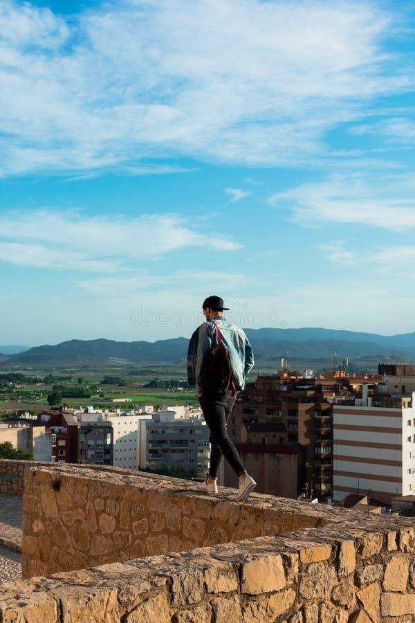 Tillbaka sikt av den unga mannen som ser staden fr?n slotttak fotografering för bildbyråer