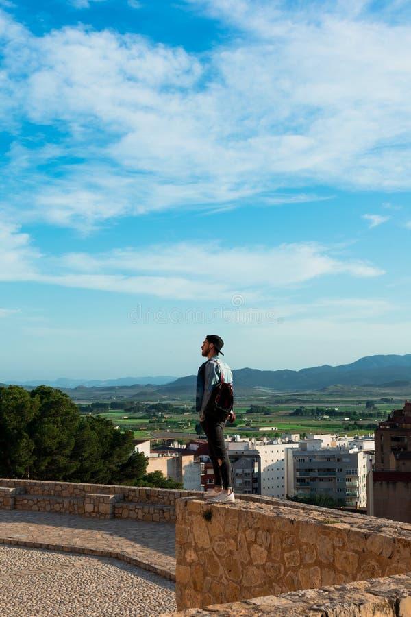 Tillbaka sikt av den unga mannen som ser staden fr?n slotttak royaltyfri fotografi