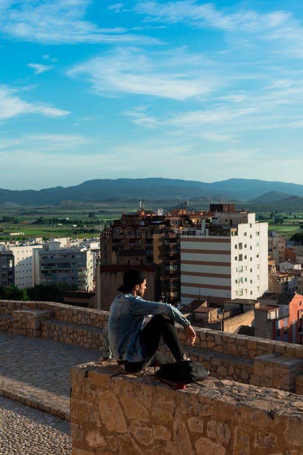 Tillbaka sikt av den unga mannen som ser staden fr?n slotttak arkivbilder
