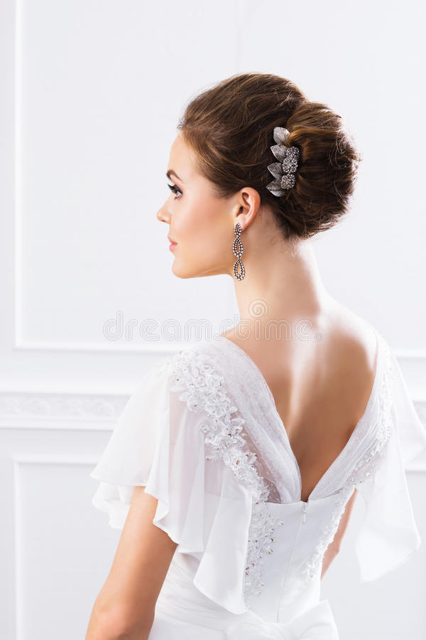 Tillbaka sikt av den unga och härliga bruden i den vita klänningen royaltyfria foton
