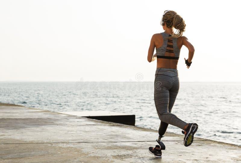 Tillbaka sikt av den unga rörelsehindrade kvinnan med det prosthetic benet royaltyfri foto