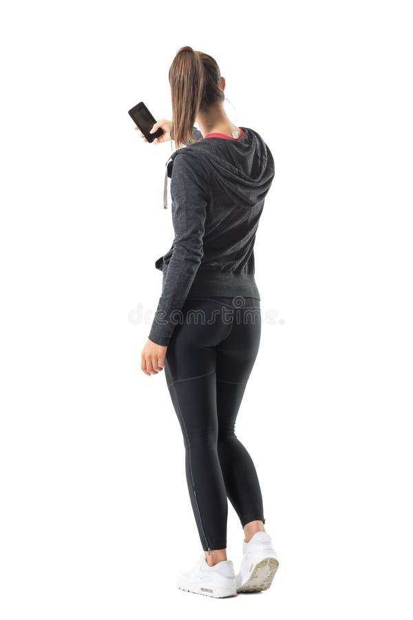 Tillbaka sikt av den unga sportiga passformkvinnan som tar fotoet med smartphonen arkivfoto