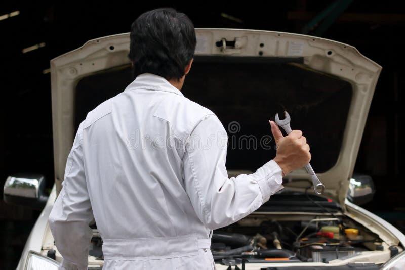 Tillbaka sikt av den yrkesmässiga unga mekanikermannen i enhetlig innehavskiftnyckel mot bilen i öppen huv på reparationsgaraget royaltyfria bilder