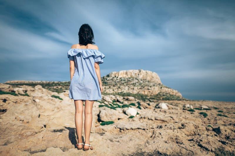 Tillbaka sikt av det ensamma kvinnaanseendet på stenig öken arkivbilder